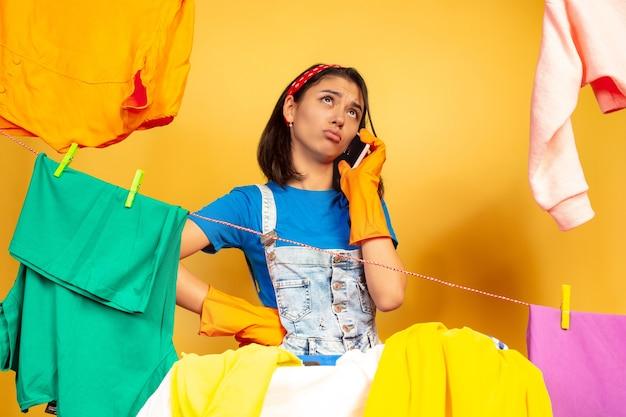 Grappige en mooie huisvrouw die huishoudelijk werk doet dat op gele achtergrond wordt geïsoleerd. jonge blanke vrouw omringd door gewassen kleren. huiselijk leven, heldere kunstwerken, huishoudelijk concept. praten aan de telefoon.
