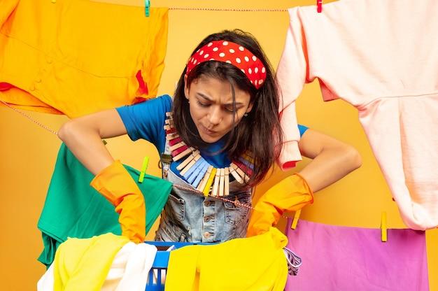 Grappige en mooie huisvrouw die huishoudelijk werk doet dat op gele achtergrond wordt geïsoleerd. jonge blanke vrouw omringd door gewassen kleren. huiselijk leven, heldere kunstwerken, huishoudelijk concept. ziet er druk uit.