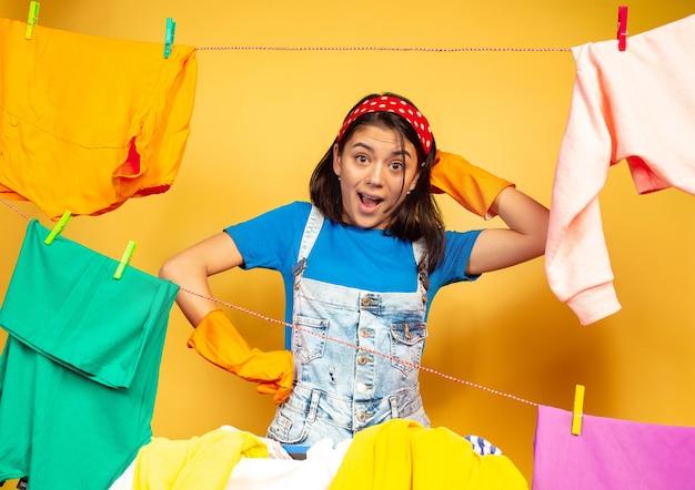 Grappige en mooie huisvrouw die huishoudelijk werk doet dat op gele ruimte wordt geïsoleerd. jonge blanke vrouw omringd door gewassen kleren