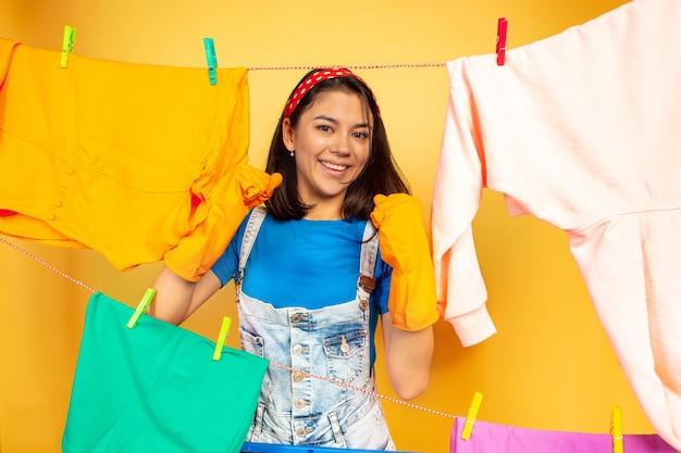 Grappige en mooie huisvrouw die huishoudelijk werk doet dat op gele ruimte wordt geïsoleerd
