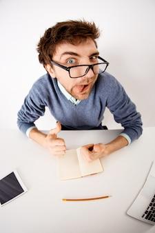 Grappige en speelse jonge zakenman in glazen, bureau zitten, inspiratie opdoen, ideeën in notitieboekje opschrijven, tong tonen en vinger wijzen