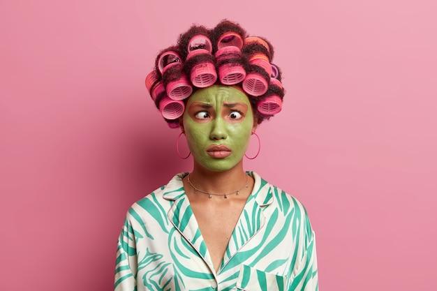 Grappige etnische jonge vrouw maakt grimas, kruist de ogen, past haarrollers toe, maakt kapsel voor speciale dag, draagt groen hydraterend masker op gezicht