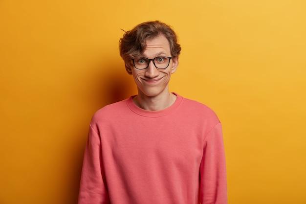 Grappige europese man heeft tevreden uitdrukking, glimlacht vreugdevol, draagt een optische bril en een roze trui, hoort goed nieuws, geïsoleerd over gele muur, drukt goede emoties uit. mannelijke nerd in bril