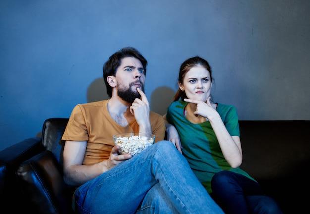 Grappige familie die thuis op de bank zit te kijken naar films popcorn-emoties