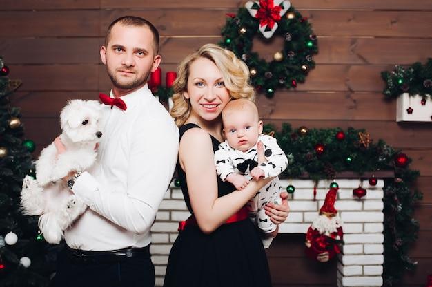 Grappige familie die zich dichtbij de hond en de zoon van de open haardholding in handen en het glimlachen bevinden