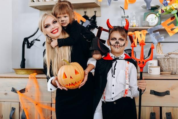 Grappige familie in de keuken die zich in kostuum bevindt en de camera bekijkt halloween