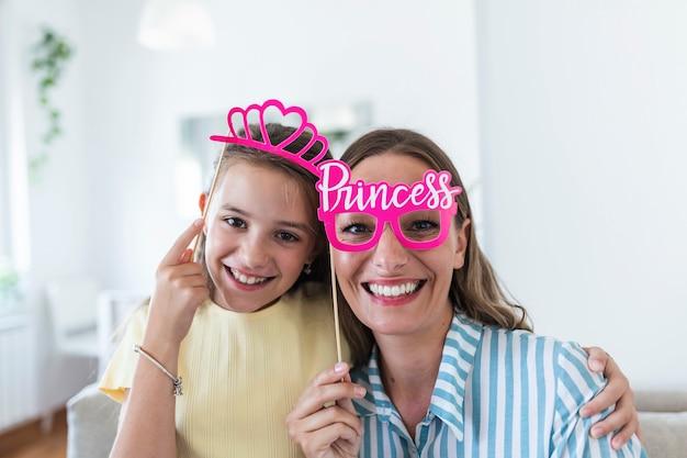 Grappige familie op een achtergrond van lichte muur. moeder en haar dochtermeisje met papieren accessoires. moeder en kind houden papieren kroon op stok.