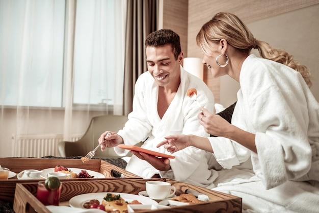 Grappige film. vrouw en echtgenoot lachen tijdens het kijken naar grappige film en eten in de ochtend