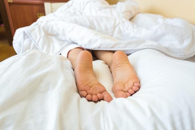Grappige foto op bed van meisjesvoeten die op kussen liggen