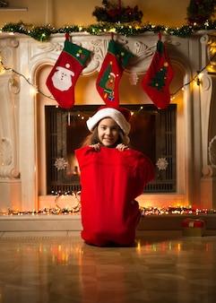 Grappige foto van een klein meisje dat in een grote rode tas zit voor cadeaus op kerstavond