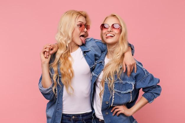 Grappige foto van jonge mooie vrolijke witharige dames die elkaar knuffelen en vreugdevol tongen steken terwijl ze over roze achtergrond in jeansjassen staan
