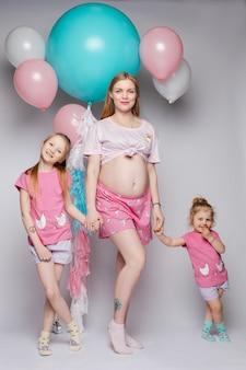 Grappige foto van prachtige zwangere moeder met twee dochters kijken naar hun buik.