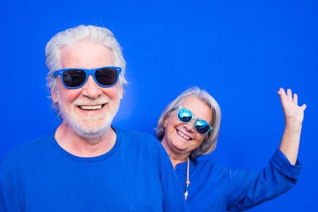 Grappige foto van twee gelukkige en leuke volwassen mensen die samen plezier hebben met het dragen van blauwe kleding en een zonnebril met blauwe achtergrond - geluk senior of gepensioneerde glimlachend en kijkend naar de camera