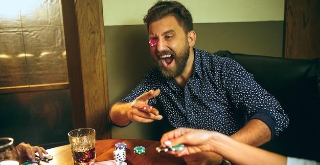 Grappige foto van vrienden die bij houten lijst zitten. vrienden plezier tijdens het spelen van bordspel.