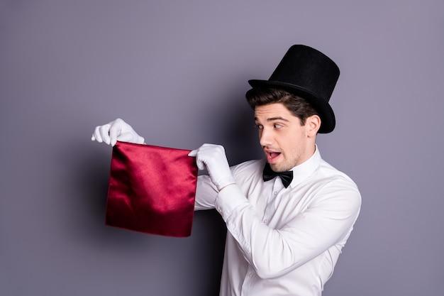 Grappige funky goochelaar start zijn prachtige focus hand vasthouden rood servet kijken zeggen abracadabra dragen wit overhemd zwarte vlinderdas hoed geïsoleerd over grijze kleur muur