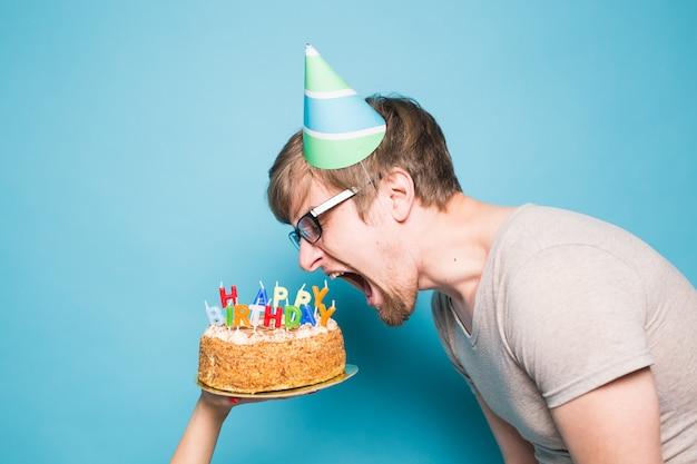 Grappige gekke jongeman in een hoed van wensdocument wil een stuk felicitatietaart afbijten. concept van gek rond en verjaardagsgroeten. kopieer ruimte