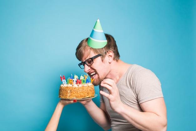 Grappige gekke jongeman in een hoed van wensdocument wil een stuk felicitatietaart afbijten