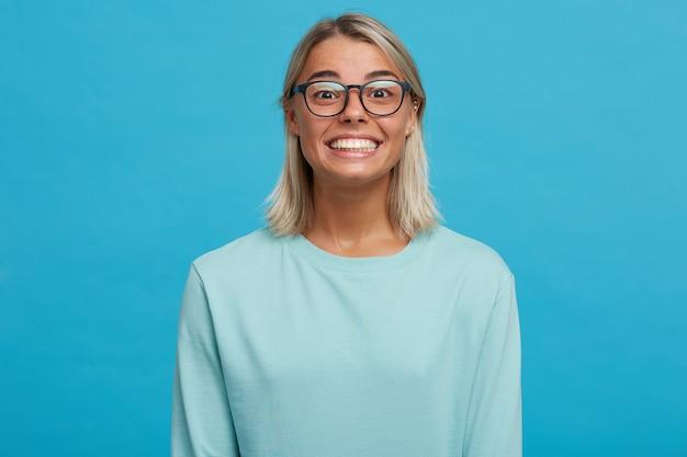 Grappige gelukkig blij blonde jonge vrouw in glazen, glimlacht wijd, schijnt van geluk, helemaal tevreden