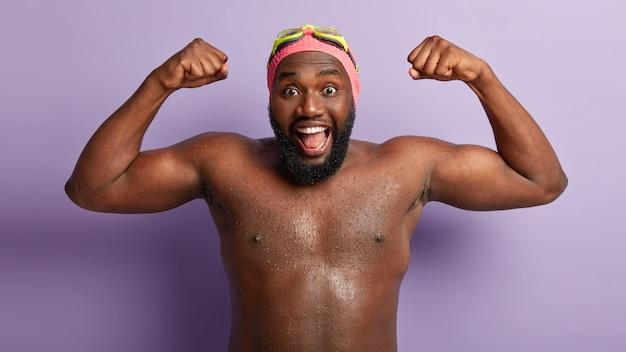Grappige gelukkig donkere man toont spieren na het zwemmen, toont nat blote sterke lichaam, heeft dikke baard