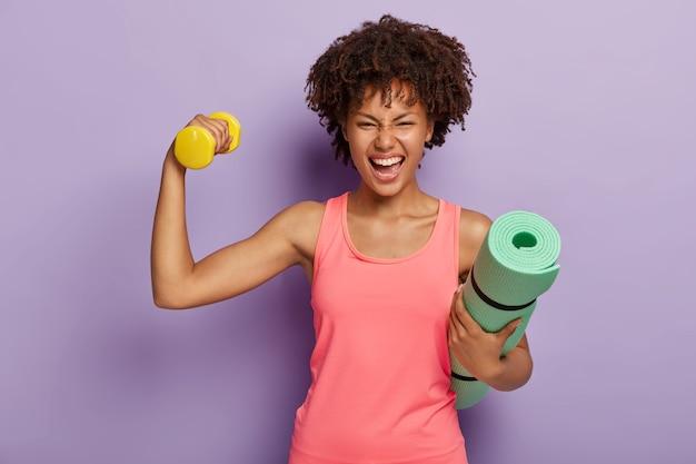 Grappige gelukkig donkere vrouw werpt hand met halter, toont biceps, houdt opgerolde fitness mat