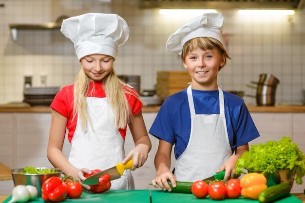 Grappige gelukkige jongen en meisje koken in de keuken van het restaurant
