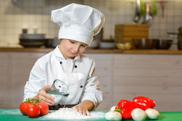 Grappige gelukkige jongen koken in de keuken van het restaurant