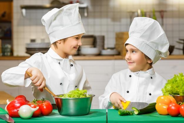 Grappige gelukkige jongens die bij restaurantkeuken koken