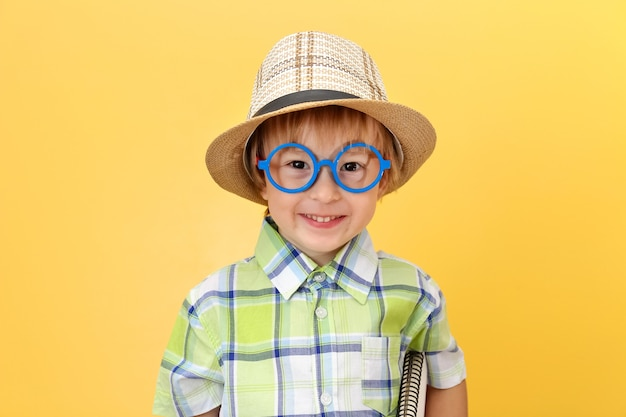 Grappige gelukkige kleine jongen in glazen en hoed glimlachen