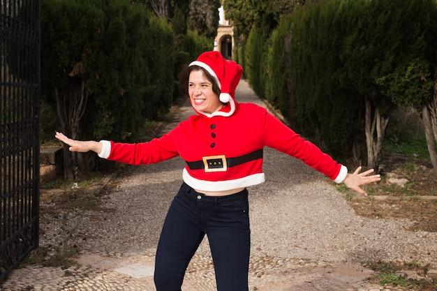 Grappige gelukkige vrouw in santa pak buitenshuis dansen