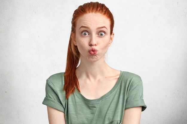 Grappige gember gember meisje rondt lippen, maakt grimas, heeft plezier alleen, draagt groen casual t-shirt, poseert tegen wit beton