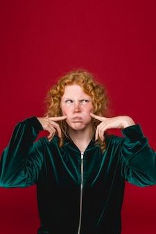 Grappige gember jonge vrouw fronsen en puffende wangen