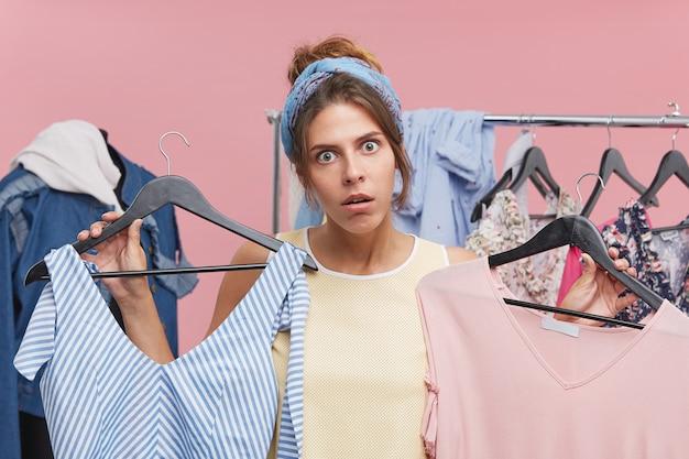 Grappige geschokte jonge vrouw die hoofdband draagt die twee hangers met modieuze kledingstukken in elke hand houdt die een wens heeft om beide te kopen terwijl het winkelen in opslag in grote verkoop. consumentisme concept