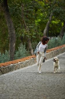 Grappige gezonde dame die in de ochtend met haar hond in park loopt
