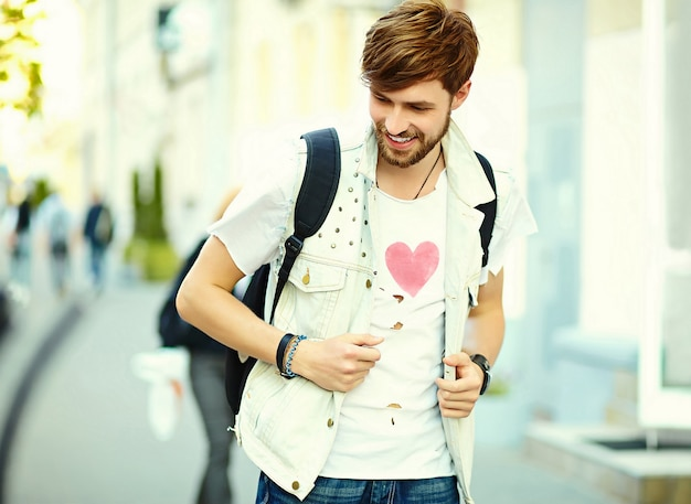 Grappige glimlachende hipster knappe mensenkerel in modieuze de zomerdoek in de straat
