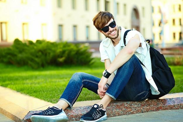 Grappige glimlachende hipster knappe mensenkerel in modieuze de zomerdoek in de straatzitting op gras in het park