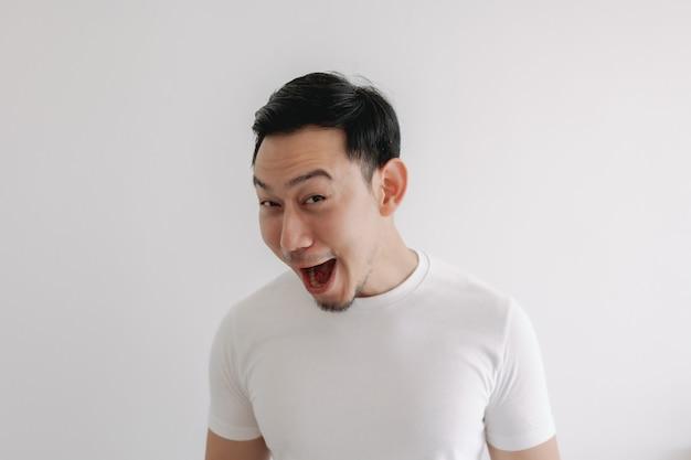 Grappige grijns glimlach gezicht van man in witte t-shirt geïsoleerd op een witte muur