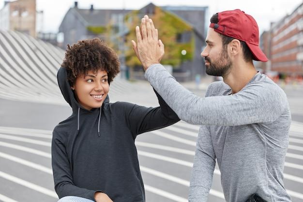 Grappige halfbloed tieners met vriendelijke uitdrukkingen geven elkaar high five, spreken af om iets te doen