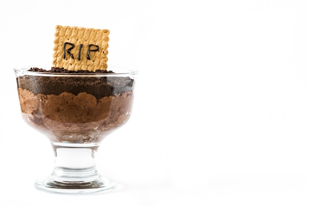 Grappige halloween-chocolademousse met grafkoekje dat op witte exemplaarruimte wordt geïsoleerd