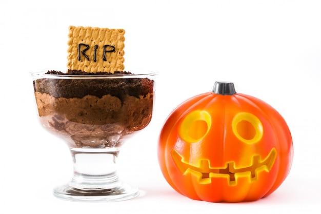 Grappige halloween-chocolademousse met grafkoekje en halloween-pompoen die op wit wordt geïsoleerd
