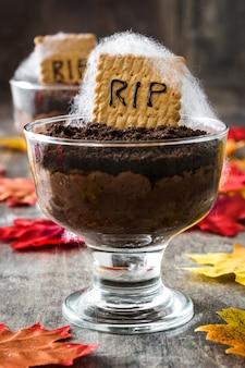 Grappige halloween-chocolademousse met grafkoekje op houten lijst
