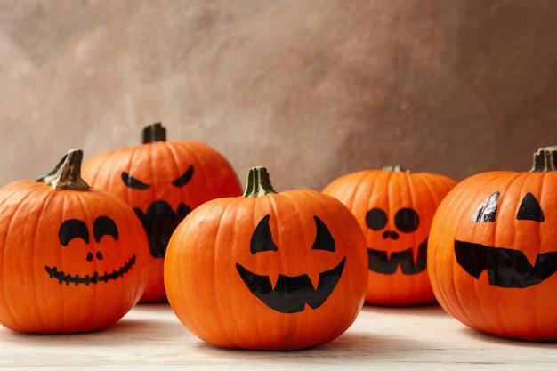 Grappige halloween-pompoenen tegen bruin, ruimte voor tekst