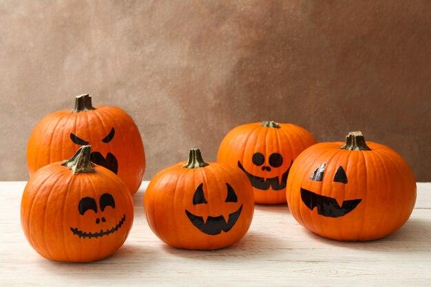 Grappige halloween-pompoenen tegen bruine achtergrond, ruimte voor tekst