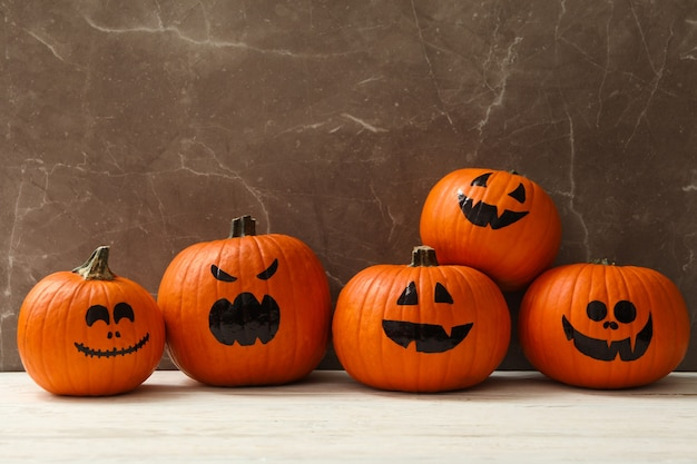 Grappige halloween-pompoenen tegen grijze achtergrond, ruimte voor tekst