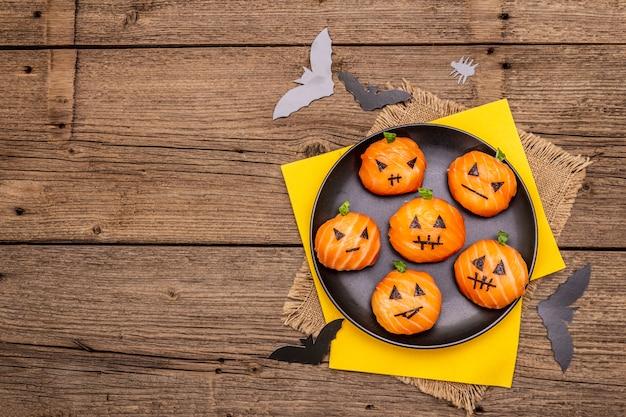 Grappige halloween-sushipompoenen jack o lantern, sushi monsters. temari sushi, sushi ballen. gezond eten voor kinderen