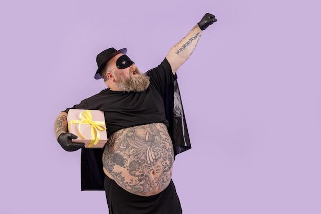 Grappige heer met overgewicht die heldenkostuum draagt, houdt aanwezig op paarse achtergrond