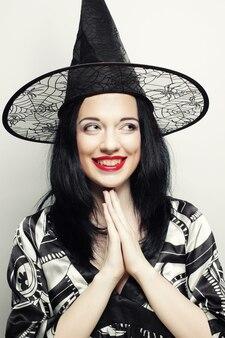 Grappige heks. jonge gelukkige vrouw met canval hoed. studio opname.