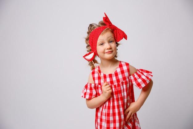 Grappige het glimlachen de zomerkleding van het babymeisje op witte achtergrond. babymeisje met een lip accessoire op een stok.