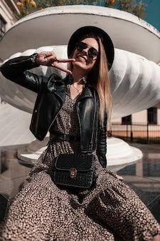 Grappige hipster meisje met zonnebril en een hoed in een stijlvolle jurk met een modieuze handtas en leren jas toont het vredesteken en zit in de stad