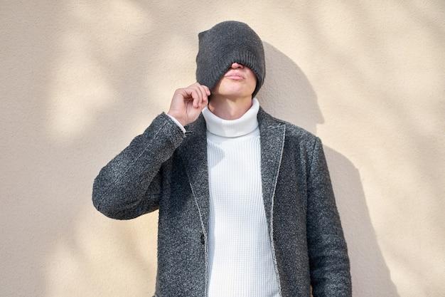 Grappige hipster stijlvolle man met het dragen van een modieuze grijze jas en witte trui gezicht met grijze hoed verbergen en poseren op beige muur