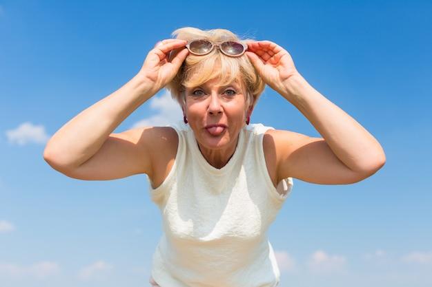 Grappige hogere vrouw haar tong uitsteekt terwijl buitenshuis poseren